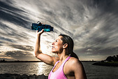Runner pouring water on herself - Stock Image - D38J57