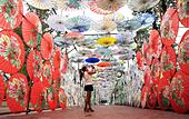 Luzhou, China's Sichuan Province. 28th Sep, 2014. A visitor takes a photo of oil-paper umbrellas at an exhibition held to celebrate the upcoming National Day which falls on Oct. 1, in Luzhou, southwest China's Sichuan Province, Sept. 28, 2014. © Liu Xueyi/Xinhua/Alamy Live News - Stock Image - E8106R