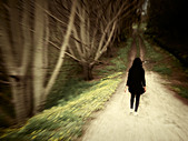 Woman walks along woodland track. - Stock Image - CNY13T