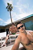 Gay couple relaxing by swimming pool - Stock Image - AHNB2P