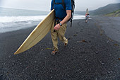 Two men hike with surfboards on The Lost Coast, California. - Stock Image - BKY28P