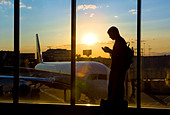 A man using his cell phone while waiting for a plane at an airport at sunset. - Stock Image - BP41W6