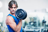 Man holding dumbbell - Stock Image - CRBE64