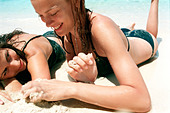 two young women lying in the sand at the beach relaxing and talking - Stock Image - AAYE68