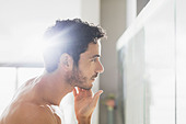 Man checking beard in bathroom mirror - Stock Image - DXT5WW