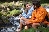 Backpacking couple take a break by a stream - Stock Image - ACDNAN