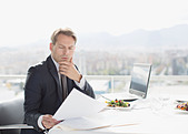 Businessman with lunch reviewing paperwork - Stock Image - D2XHRB