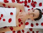 Woman covered flower petals laying on massage table - Stock Image - B77G2E