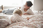 Toddler girl sitting with mother in bed - Stock Image - C8431E