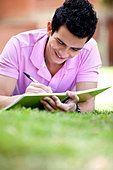 Casual guy studying outdoors lying on the floor - Stock Image - C1DHXA