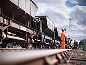 Railway workers signaling train - Stock Image - CYKXG2