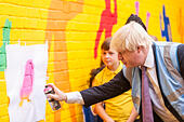 London, UK. 16 July 2015. The Mayor of London, Boris Johnson, visits Marcus Garvey Park near Hammersmith to join local volunteers clearing the park, assisting local schoolchildren to paint a colourful wall mural and to officially launch the start of this summer's biggest ever Capital Clean-up. The initiative, funded by the Mayor of London, aims to improve previously neglected areas of the city with the help of nearly 3,000 volunteers. © Stephen Chung/Alamy Live News - Stock Image - EXP9XG