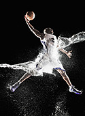 African American basketball player splashing in water - Stock Image - D6E96D
