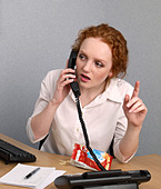 Young woman on telephone at her office desk with bag of lo fat crisps Trying to attract the attention of a colleague - Stock Image - B62G1K