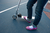Girl wearing pink sandals riding a scooter - Stock Image - CEW7AH