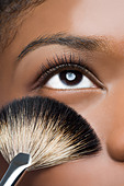 Woman with makeup brush near eye - Stock Image - BHG8KX