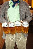 Waiter holding 4 Mass beer jugs Oktoberfest Munich Germany - Stock Image - D6H763