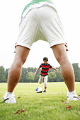 Father and son playing soccer in the park - Stock Image - AMDG9K
