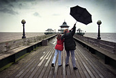A GIRL AND HER MOTHER STRUGGLE WITH A BLACK UMBRELLA DURING A WALK ON CLEVEDON PIER NORTH SOMERSET UK - Stock Image - AP6JC7