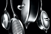 different shape and sizes aluminum stainless steel pots and pans shot in a moody edgy light against black background - Stock Image - DWENE4