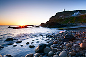 A clear evening sky and the last rays of sunlight highlight the small rocky beach at Priest's Cove Cape Cornwall - Stock Image - BY4HNW