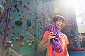 Smiling woman holding climbing rope at gym - Stock Image - DA7122
