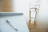 Notepad with a pen lying on it and glass of water on a table - Stock Image - ATYY6K