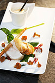 Fried monkfish with mushrooms, cappuccino in background - Stock Image - BJHXWP