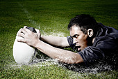 Rugby player on wet field - Stock Image - C991NN