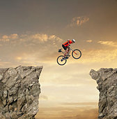 Mixed race bicyclist jumping over canyon - Stock Image - CYKJ5T