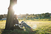 Woman relaxing with dog in park - Stock Image - D2ABBA