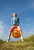 Young girl bouncing on a Space Hopper, England UK - Stock Image - AEC2RN