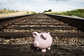 Piggy bank on railroad tracks - Stock Image - D2AB1M