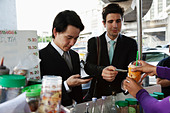 Businessmen buying lunch together at food cart - Stock Image - C6EP41