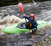 A canoeist on a river in the UK - Stock Image - B63NXX