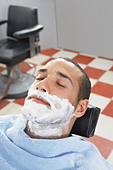 Man with shaving foam on face at barbers - Stock Image - BDNTAY