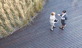 High angle view of businesswomen discussing while standing on floorboard - Stock Image - EWFC6A