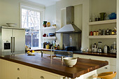 Iroko wood worktop on island in kitchen with open shelving - Stock Image - C44975
