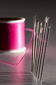 Row of sewing embroidery needles with red thread and shadows with bobbin - Stock Image - CW2H4P