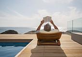 Older man reading by pool - Stock Image - DKPNDM