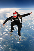Skateboarder high above the clouds performing a trick - Stock Image - C0BFWH