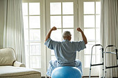 Senior African American man on fitness ball at home - Stock Image - E14R1P