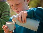 Close up of young boy pouring water from insulated flask - Stock Image - BKXF75