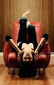 Woman sitting upside down listening to music - Stock Image - AGR198