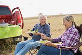 Senior couple enjoying lunch in crop field - Stock Image - E89GWA