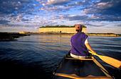 Woman paddling a canoe. - Stock Image - AJ935T