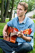 Guy playing guitar outdoors - Stock Image - BKWFHK