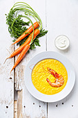 Carrot soup with shrimp on white wooden background - Stock Image - DDCP14