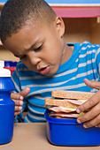 Boy looking at lunch box - Stock Image - BJRDNT