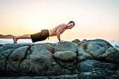 Mid adult man doing push-ups on rocks at beach - Stock Image - E708E6